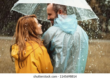 Joyful man strolling with woman in rain. They are looking at each other with content and love