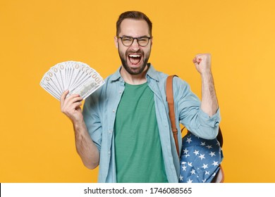 Joyful man student in casual clothes glasses backpack isolated on yellow background. Education in high school university college concept. Hold fan cash money in dollar banknotes, doing winner gesture