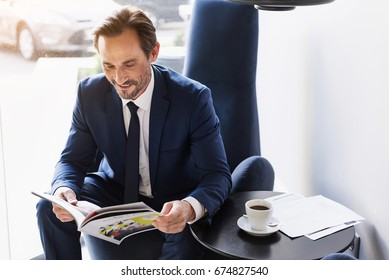 Joyful man in suit entertaining with journal in cafe