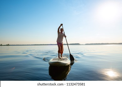 Joyful man is training on a SUP board on a large river during sunny morning. Stand up paddle boarding - awesome active recreation in nature. Backlight.