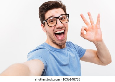 Joyful man in t-shirt and eyeglasses making selfie and showing ok sign while looking at the camera over grey background