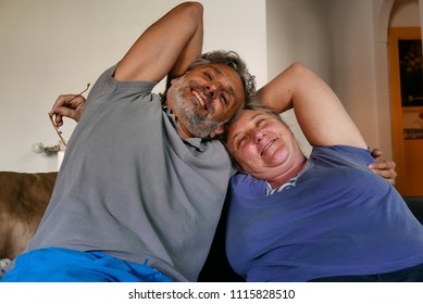 joyful mature couple on the couch at home