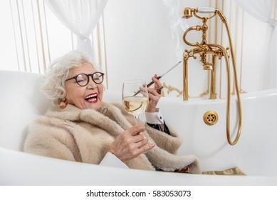 Joyful mature lady relaxing in bathtub