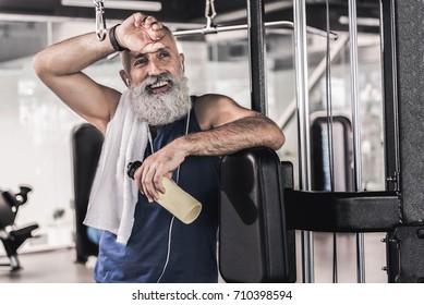Joyful mature male having rest after workout in sport center