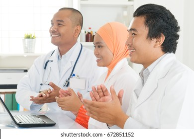 Joyful medical team clapping hands during a meeting, Southeast Asian Muslim doctors and nurses.