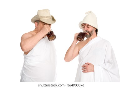 Joyful men in traditional bathing costumes drink kvas - russian bread juice. From a series of Russian bath