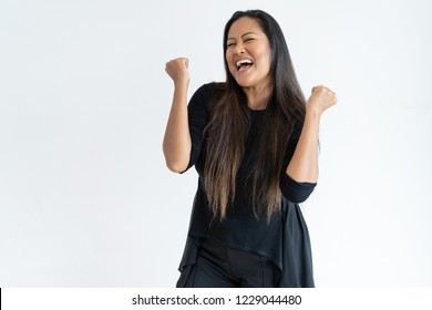 Joyful middle-aged woman celebrating success. Lady pumping fists with her eyes closed. Success concept. Isolated front view on white background.