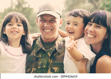 Joyful military man posing for camera with his wife, holding kids in arms, children waving hello. Medium shot. Family reunion or returning home concept