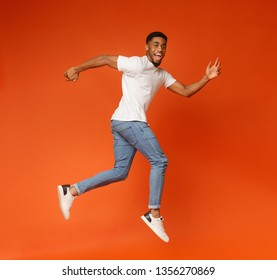 Joyful millennial african-american guy walking on air, jumping on orange studio background, smiling at camera
