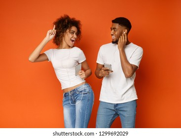 Joyful millennial black man and woman in earphones listening to music on cellphones and smiling to each other, orange background