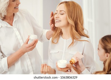 Joyful moment. Radiant mature blonde lady sitting on a chair and beaming while enjoying the time spent with family and taking care of her face skin together with a loveful grandmother and daughter
