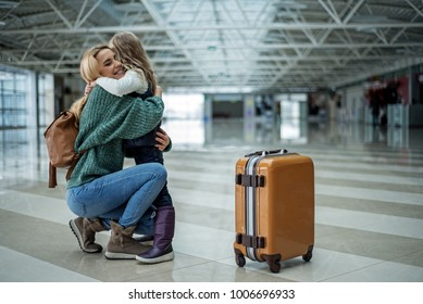 Joyful mommy meeting little daughter after long flight. They are in a strong hug