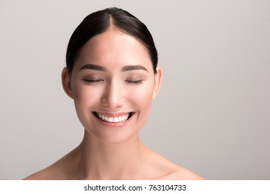 Joyful mood. Close-up portrait of positive young asian woman with clean and fresh skin is standing with closed eyes and feeling happy. Isolated background