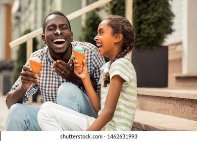 Fröhliche Stimmung. Emotionaler junger Mann, der sein Lächeln demonstriert, während er Eis auf der Nase hat