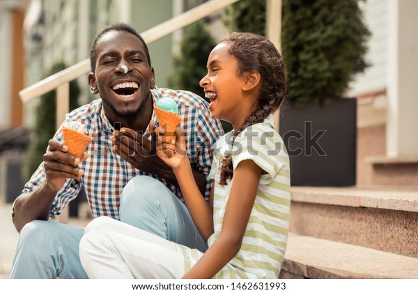 Joyful mood. Emotional young man demonstrating his smile while having ice cream on his nose