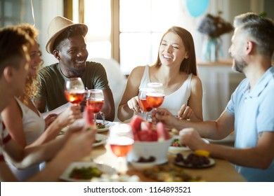 Joyful multi-ethnic friends sitting by festive table, having drinks and talking at home party