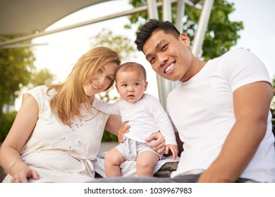 Joyful multi-ethnic parents and their little baby