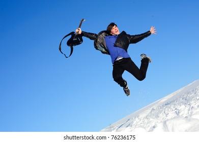 Joyful musician jumping with guitar