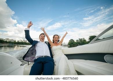 Joyful newlyweds on the boat on the lake in the wedding day