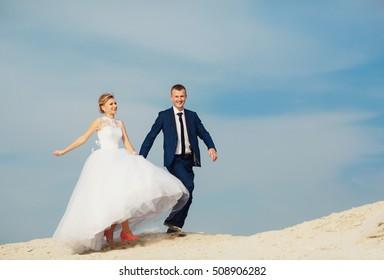 Joyful newlyweds are walking on the sand