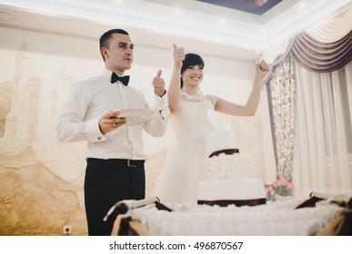 Joyful newlyweds and the wedding cake