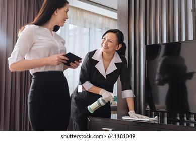 Joyful nice businesswoman talking to a hotel maid