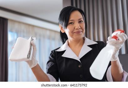Joyful nice hotel maid showing her equipment