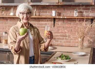 Joyful old lady prefers healthy eating