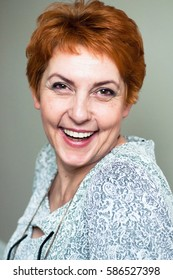 Joyful older redhead woman smiles expressly and looking at camera