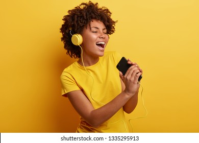 Joyful optimistic glad black woman glad to search favourite composition on web page, listens favourite cool song in headphones, sings from pleasure, has modern gadgets, wears yellow t shirt.