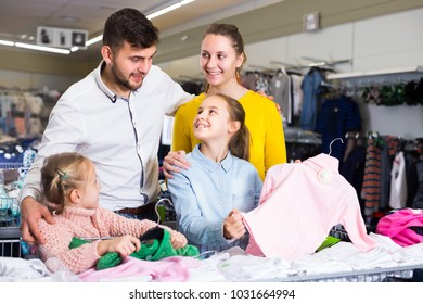Joyful parents choosing new turtleneck for daughters in children clothing shop