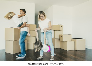 Joyful parents and kids enjoying new home, dancing and having fun near heaps of boxes in empty room. Full length. Apartment buying concept