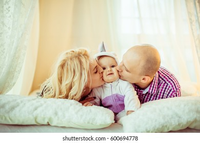 Joyful parents kiss their little daughter lying on soft bed