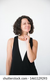 Joyful pensive customer thinking over sale special offer. Happy middle aged business woman touching chin with finger and smiling at camera. Advertising concept