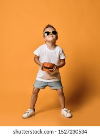 Joyful and pleased kid boy in stylish sunglasses, white t-shirt and blue jeans shorts is posing with a big burger cheeseburger in his hands boasting on yellow background