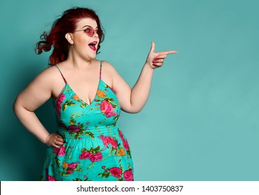 Joyful plus-size overweight redhead lady in sunglasses and sundress shows a gesture sign finger - gun like saying Yeah! or You are lucky, aimed, point at mint background with free text copy space