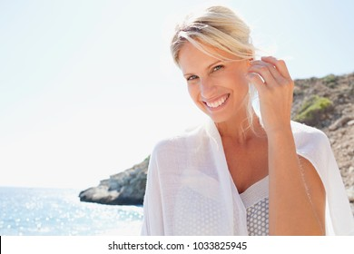 Joyful portrait of beautiful tourist woman relaxing on sunny sky holiday beach with white fabric wrapped around her, smiling looking in nature outdoors. Healthy wellness leisure recreation lifestyle.
