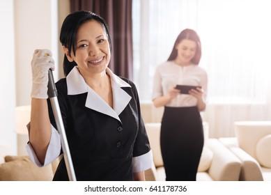 Joyful positive hotel maid smiling