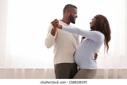 Joyful pregnant couple having fun, dancing next to window at home, free space
