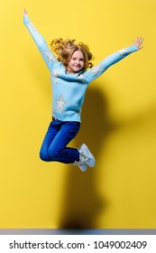 Joyful pre-teen girl jumping over yellow background. Full length studio shot. Happiness, activity and child concept.
