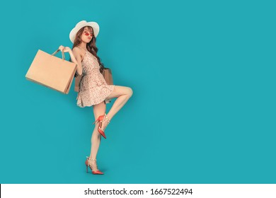 Joyful pretty Asian girl carrying shopping bags with summer dress and enjoys shopping.