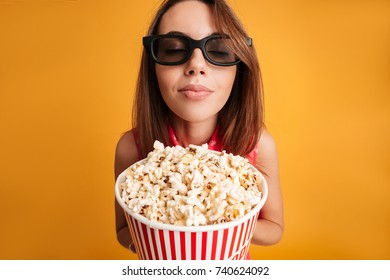 Joyful pretty girl in red dress standing with closed eyes, holding popcorn, isolated on yellow background