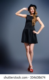 Joyful pretty girl wearing black dress and black classic hat posing at studio. Full length portrait.  Beauty, fashion concept. Hipster style.