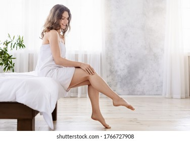 Joyful pretty lady wrapped in towel sitting on bed, touching her legs skin, body care concept, empty space