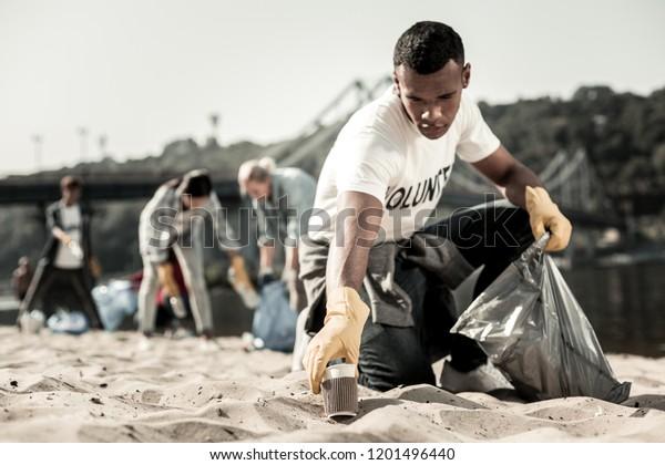Alegre el proceso. Simpático estudiante responsable de pelo oscuro disfrutando del proceso de voluntariado mientras limpia la basura