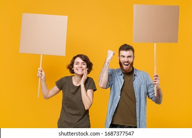 Joyful protesting two people guy girl hold protest signs broadsheet blank placard on stick doing winner gesture isolated on yellow background. Protests strikes pickets concept. Youth against city