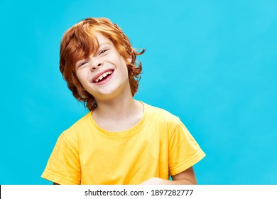 Joyful red-haired boy with a wide smile in a yellow T-shirt head tilted to one side