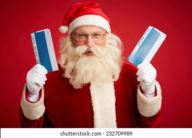 Joyful Santa Claus with two airline tickets over red background