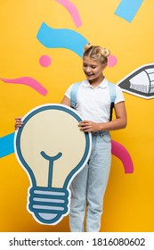 joyful schoolchild holding light bubble maquette on yellow background with colorful elements and paper cut pencil