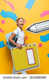 joyful schoolchild looking at camera while holding copy book maquette near paper pencil and abstract elements on yellow